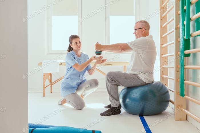 Young professional physiotherapist exercising with an injured patient using a blue ball