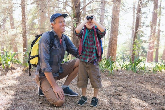 Happy man watching boy looking through binoculars