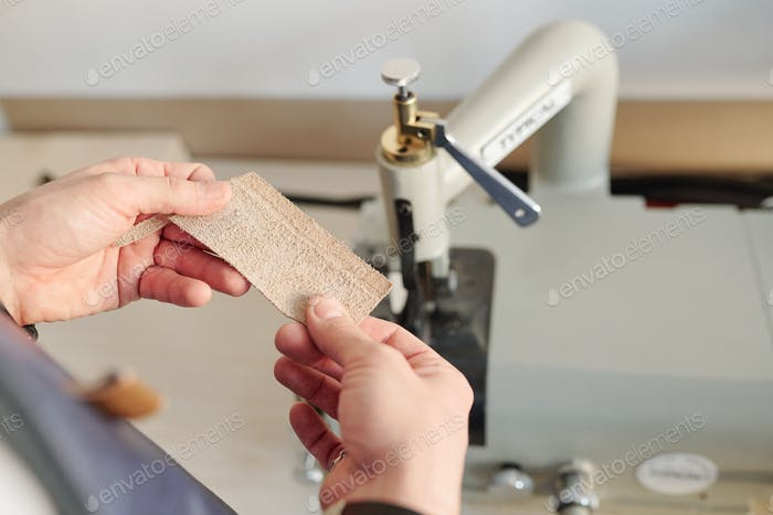 Hands of young creative craftsman holding small piece of blond suede
