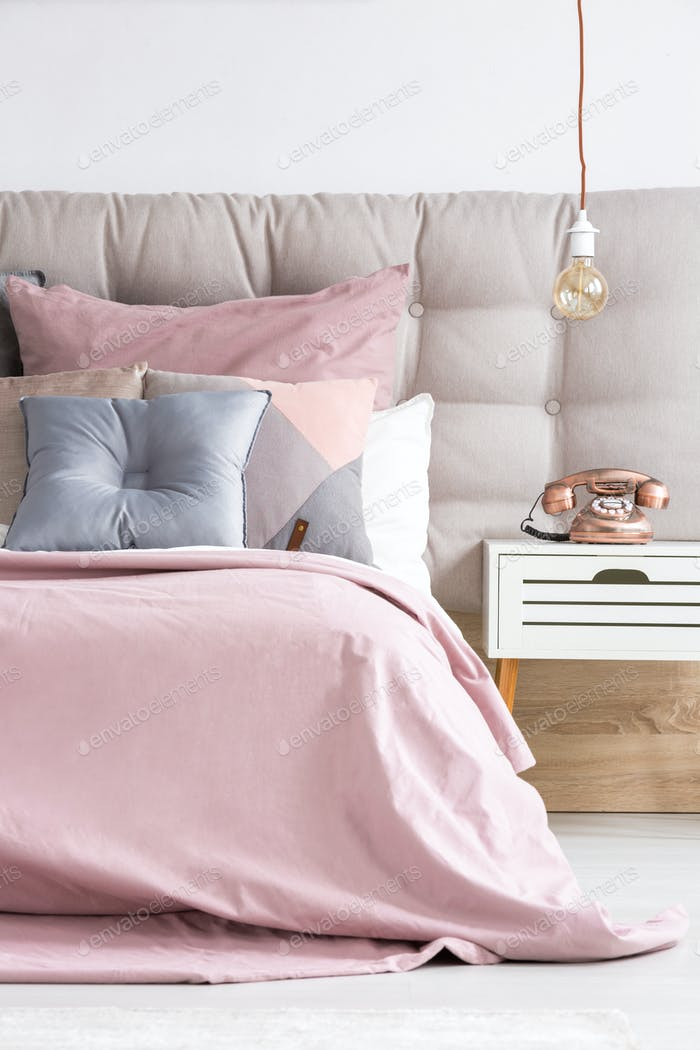 Bed with soft pink coverlet