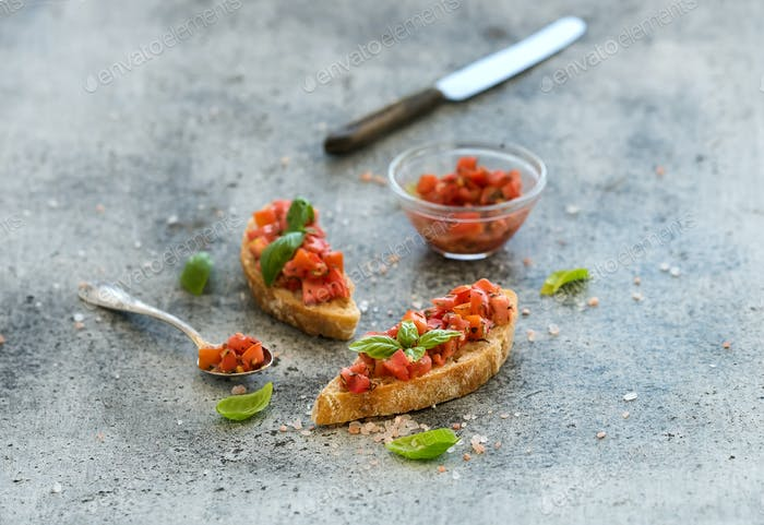 Tomato and basil bruschetta sandwich over grunge gray background.