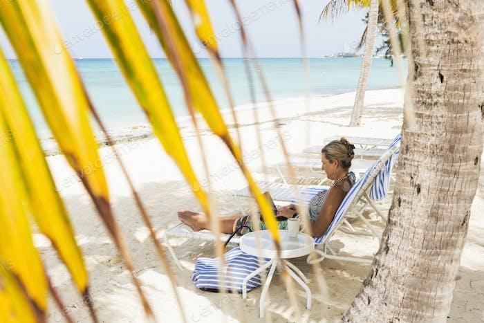 adult woman executive using laptop on the beach, Grand Cayman Island