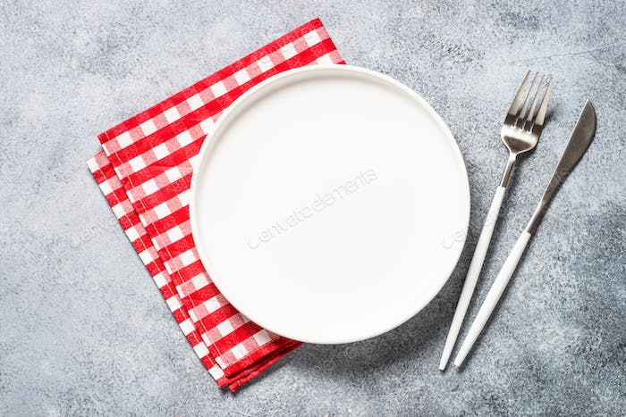 Table setting with white plate and cutlery top view