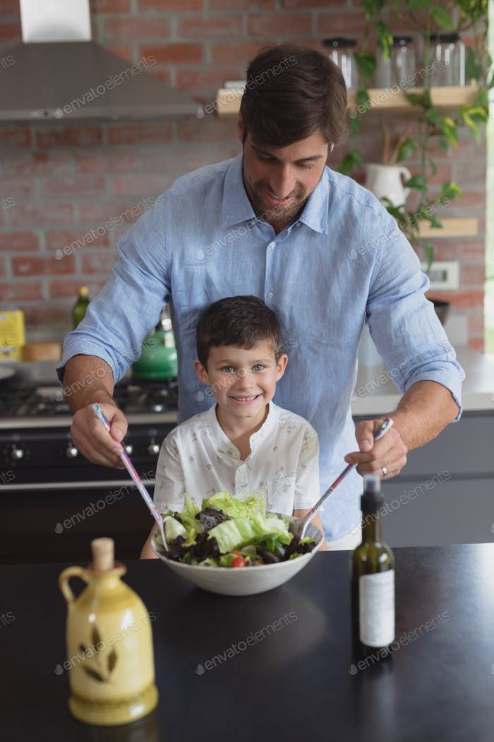 Front view of Caucasian father and son preparing vegetable salad in kitchen at home