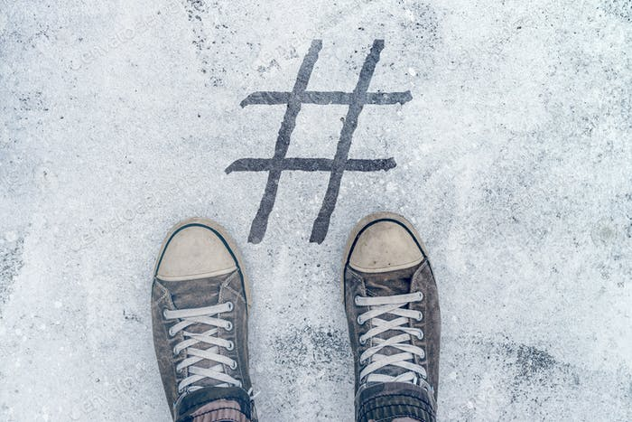 Feet standing over hashtag imprint on street