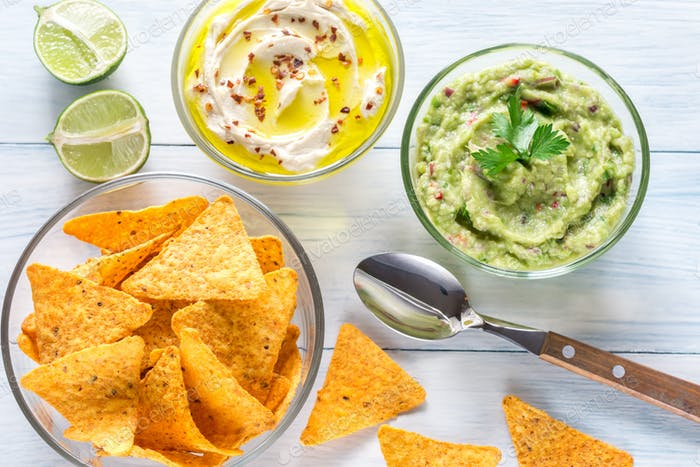 Bowls of hummus and guacamole with tortilla chips