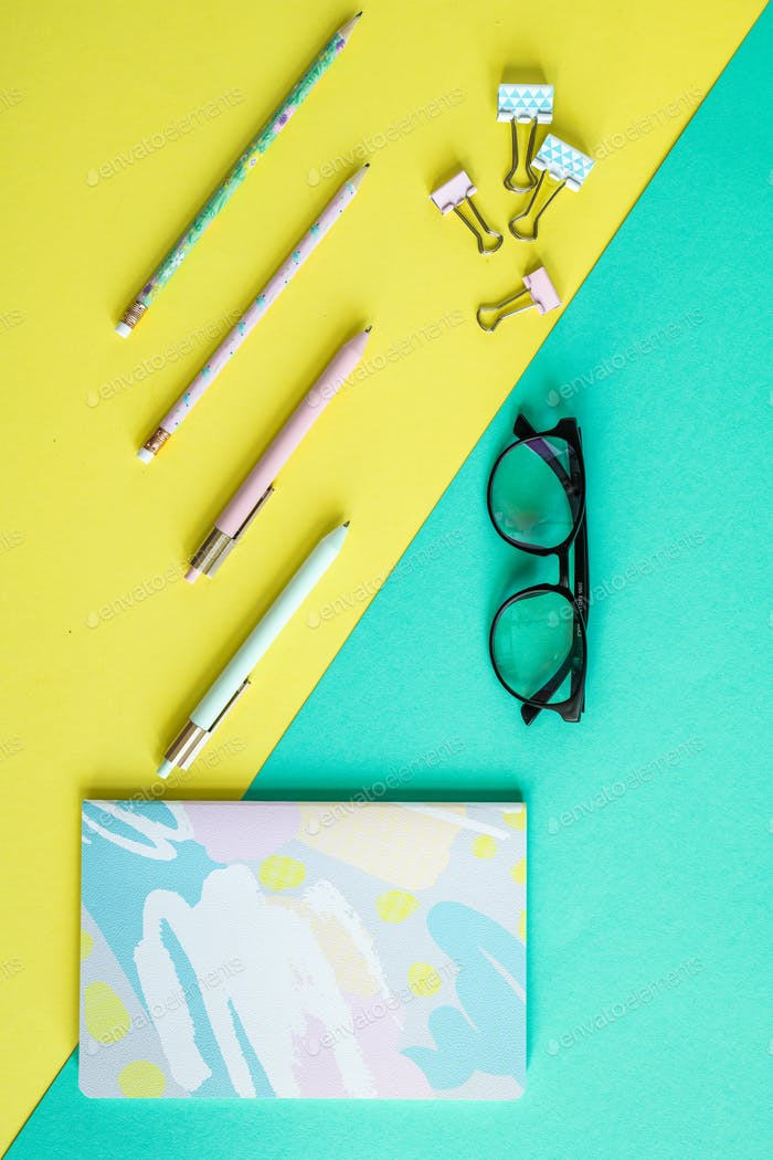 Overview of pens, clips, notebook and eyeglasses on yellow and blue background
