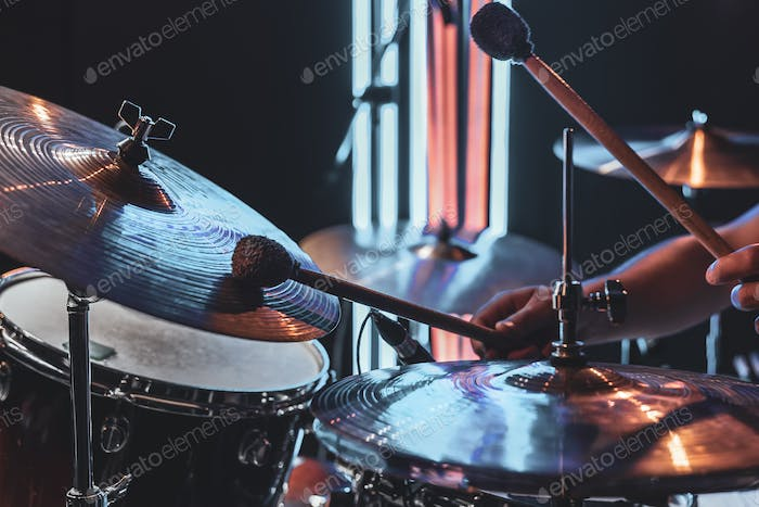 A male drummer plays drums with special drum sticks.