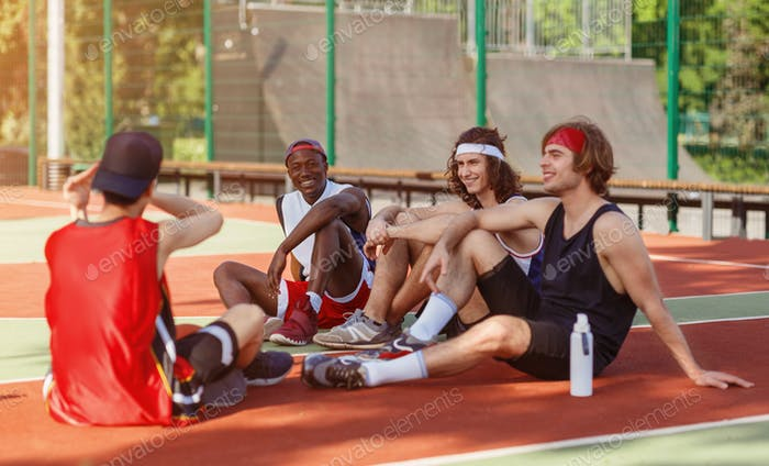 Multiethnic basketball team resting on outdoor arena after their game