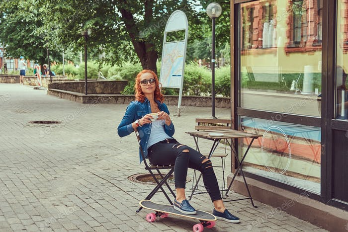 Redhead girl drinks a coffee, sitting near a coffee shop, relaxing after riding a skateboard.