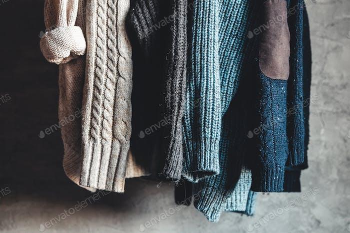 Sammlung von warmen Pullovern hängen auf Rack vor grauem Hintergrund, Nahaufnahme