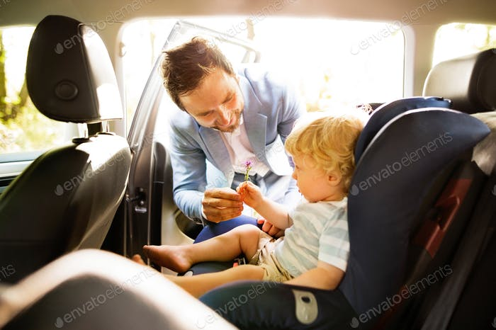 Father putting his son in the car.