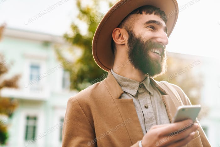 Atractivo hombre joven sonriente que lleva abrigo de otoño