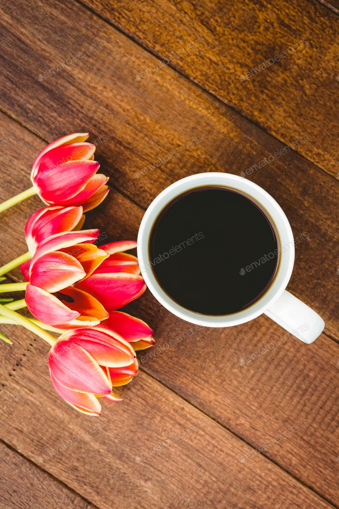 Red flowers and a cup of coffee on wood desk