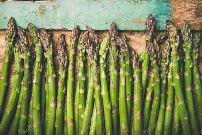 Raw uncooked green asparagus over rustic wooden tray background, close-up