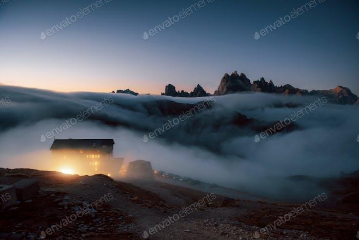 Жилой дом с огнями в окнах расположен в великолепном горном месте