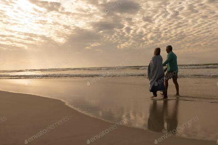 Rear view of active senior couple walking hand in hand on the beach