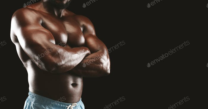 Cropped image of afro bodybuilder with arms crossed