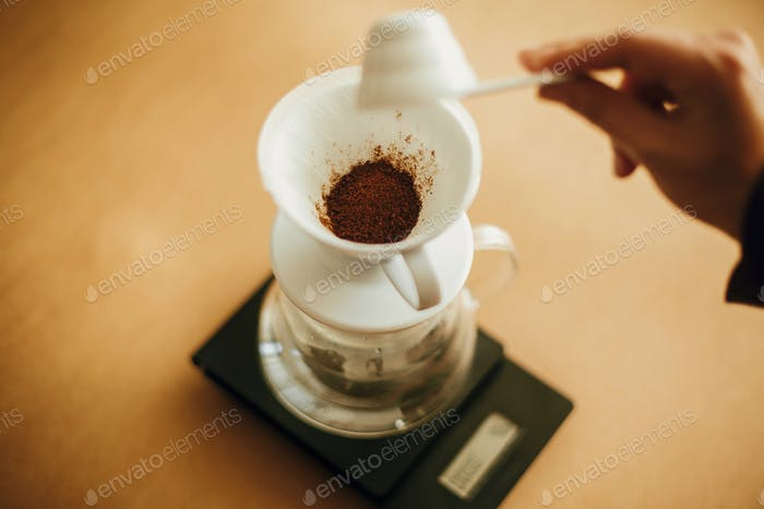 Hands pouring grounded coffee in filter pour over on glass kettle on scale