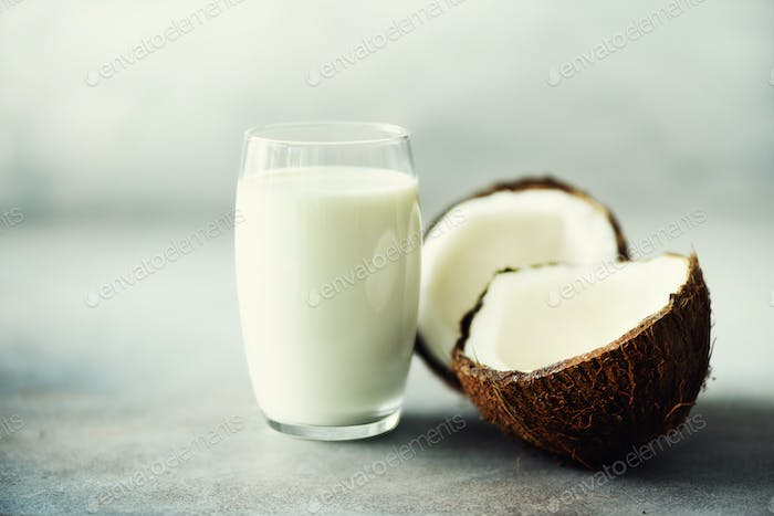 Coconut vegan milk non dairy in glass and coconut fuit halves on grey concrete background with copy
