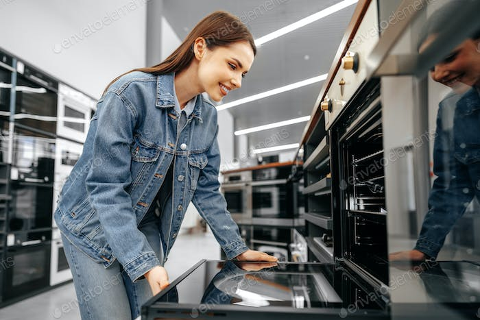 Young woman looking for new electric oven in a shopping mall