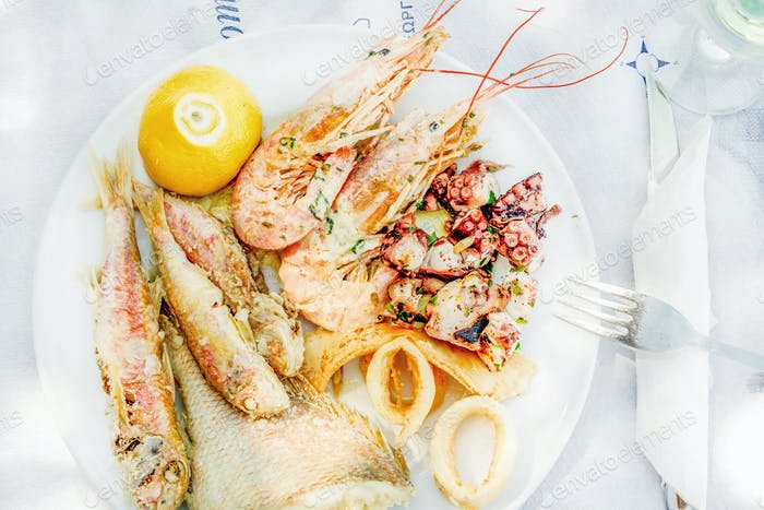 Cooked seafood on plate with lemon and wine