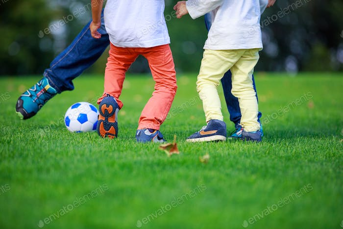"""Father and sons playing football in park"
