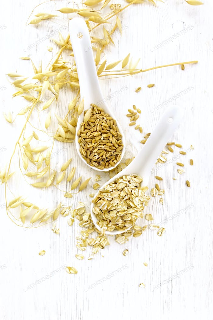 Oat flakes and grains in spoons on board top