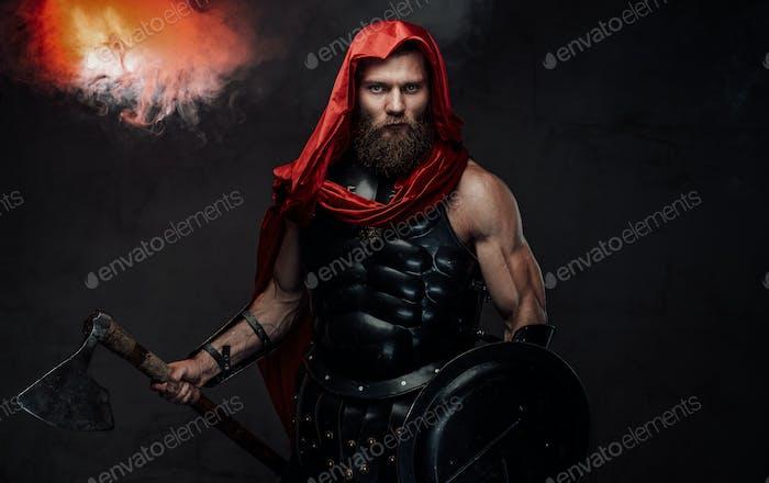 Bearded praetorian in black armor posing in smoky room