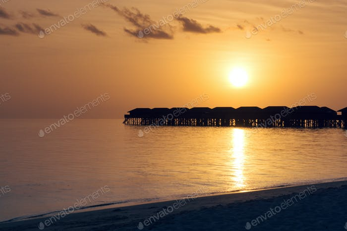 Silhouette beautiful tropical Maldives resort hotel and island with beach and sea on sunset.