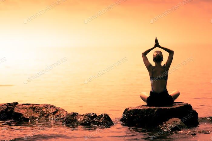 Junge Frau tun Lotus Yoga Position vor dem Ozean