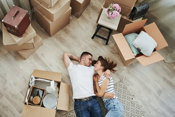 Lying down on the floor. Cheerful young couple in their new apartment. Conception of moving