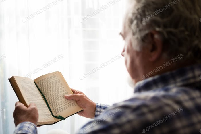 Close up senior man reading book in nursing home
