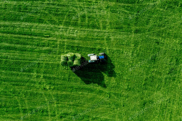 Aerial view of green grass harvest field with tractor moving hay bale