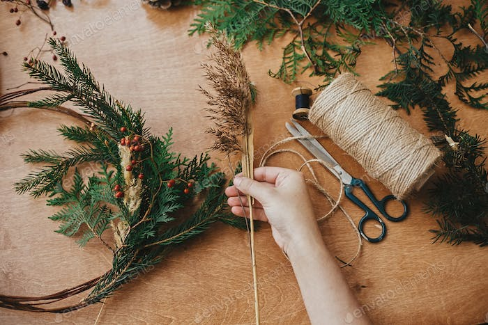 Hands holding herb, berries, fir branches, pine cones, thread, scissors on wooden table