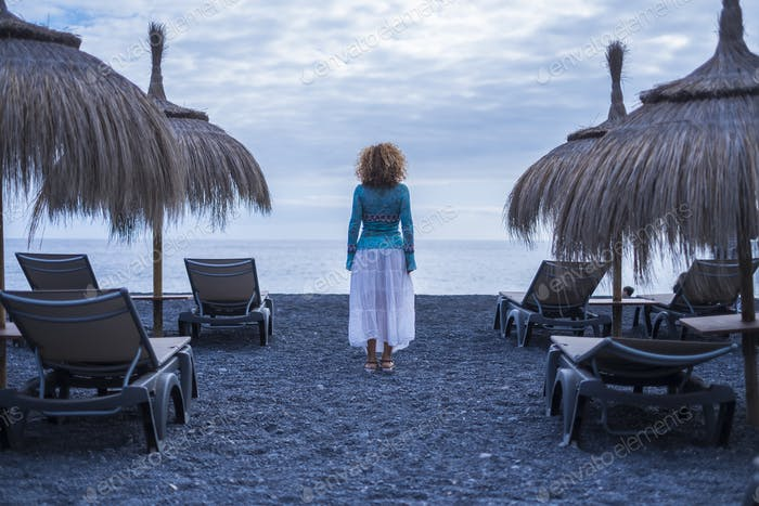lonely woman viewed from back side stand in the middle of empty seats at the beach