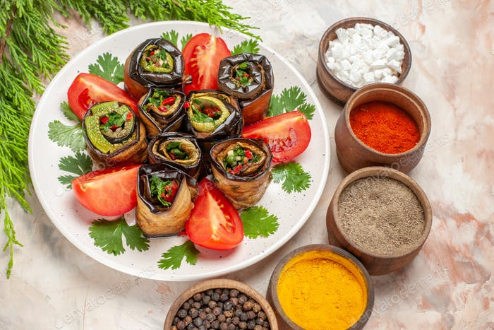 top view yummy eggplant rolls with tomatoes and seasonings on a light background food dish photo