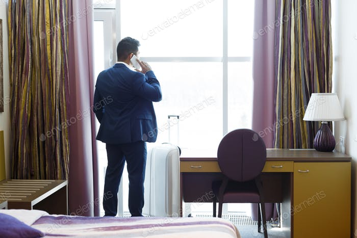 Businessman calling taxi service from hotel room, staying near window