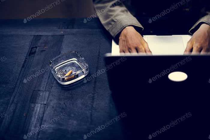 Hands using a laptop featuring a cigarette in an ashtray