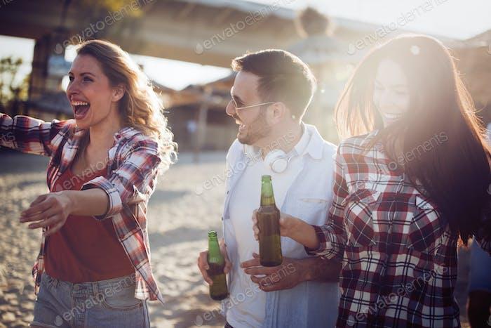 Glückliche Leute trinken und Spaß am Strand haben