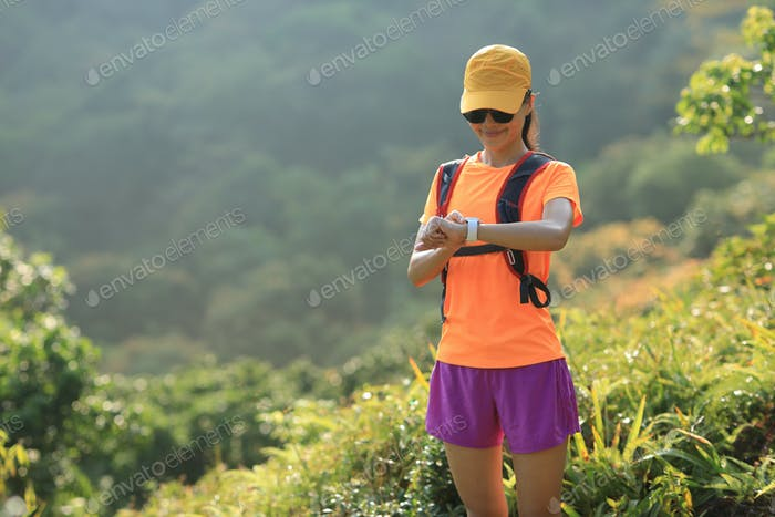 Woman trail runner set her smartwatch while running in mountains