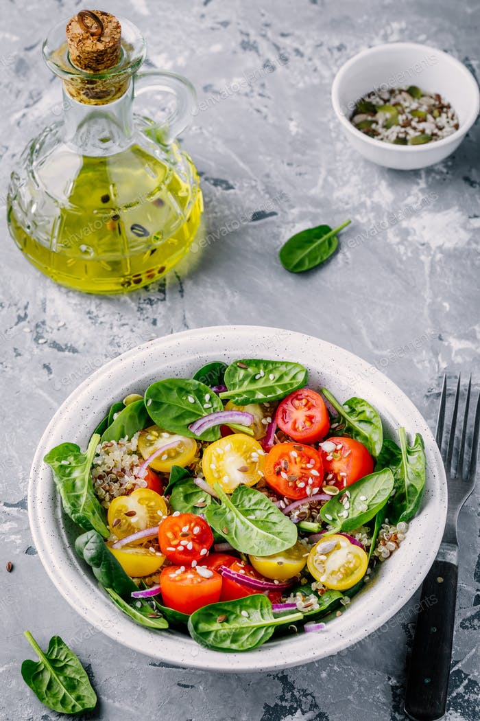 Healthy green salad with spinach, quinoa, yellow and red tomatoes, onions and seeds