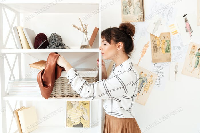 Young woman designer choosing textile material for her work