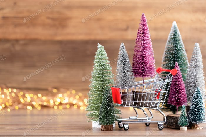 Colorful Christmas tree on wooden, bokeh background.