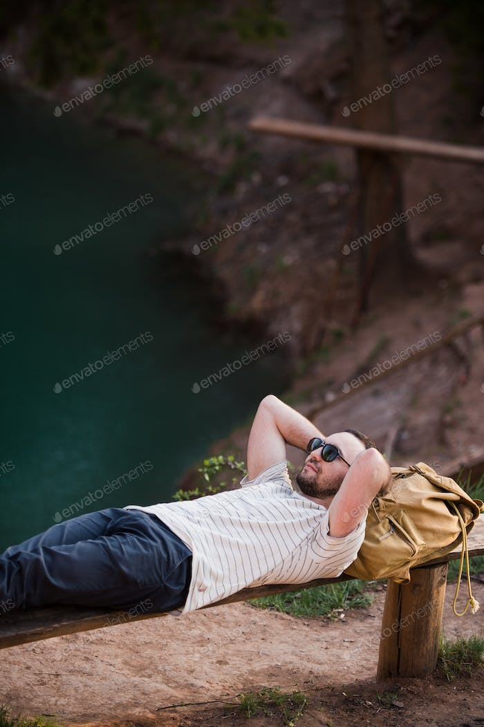 Man Relaxing Outside. Wearing a white T shirt, dark pants, sunglasses, a young guy is lying down on