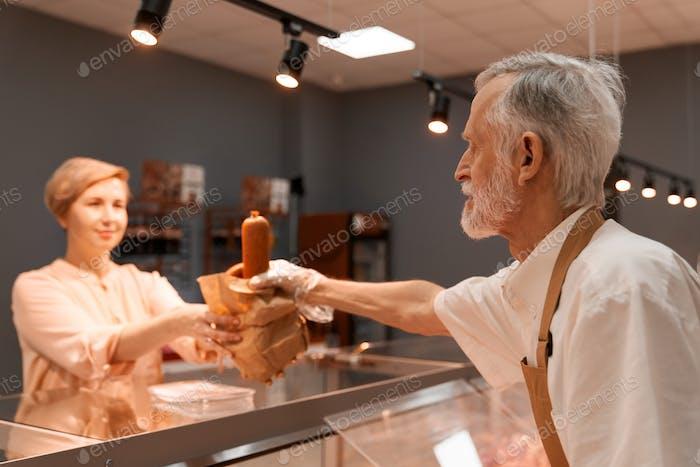 Mayor carnicero dando salchichas a señora