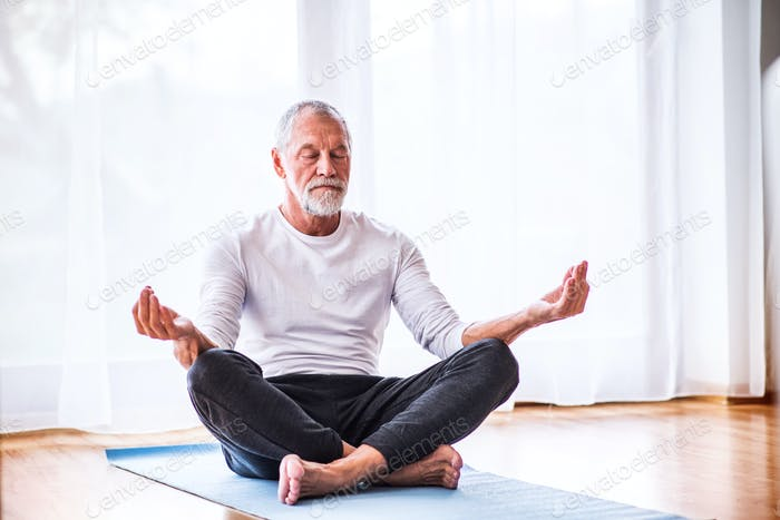 Senior man meditating at home.