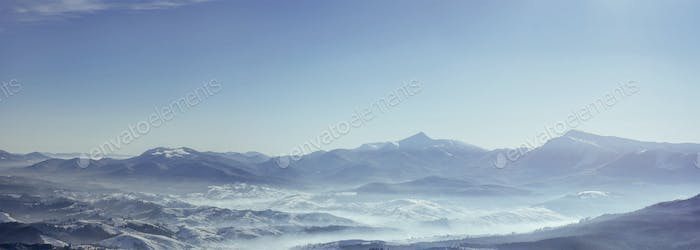 Snowy mountains peaks with mist at sunny day. Carpathian