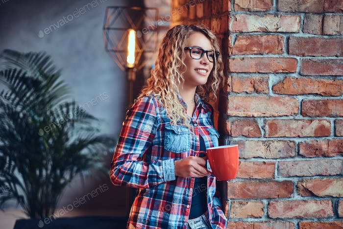A woman drinks morning coffee in a restroom with loft interior.