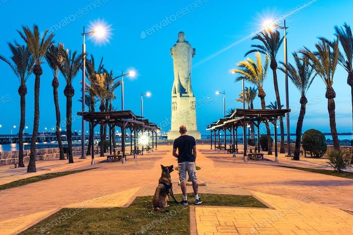 Wanderlust Mann und Hund am Cristofer Collumbus Denkmal in Spanien